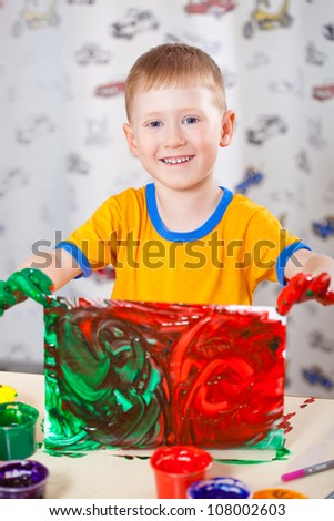little boy holding painted picture with fingerpaints - stock photo