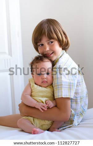 Little boy hugging and enjoying his newborn sister - stock photo