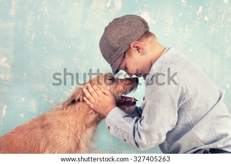 Little Boy hugging his dog - stock photo
