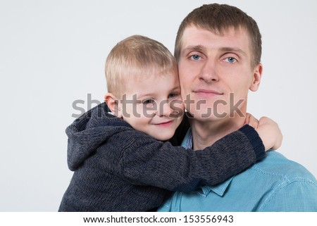 Little boy hugging his father, closeup photo in studio - stock photo