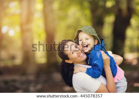 Little boy hugging his happy mother in park - stock photo