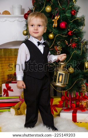 Little boy in a black suit holds a small Christmas lamp - stock photo