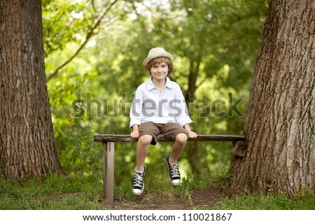 Little boy in a hat, shorts and sneakers - stock photo