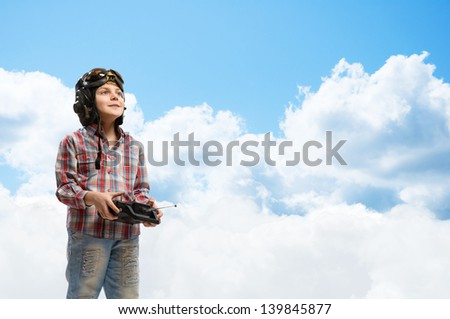 little boy in a helmet pilot keeps remote control, in the background sky and clouds - stock photo