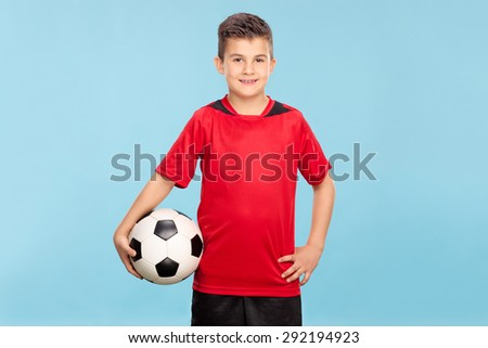 Little boy in a red jersey holding a football and looking at the camera on blue background - stock photo