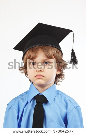 Little boy in academic hat on a white background - stock photo