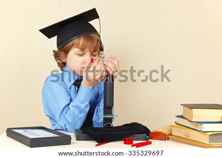 Little boy in academic hat sees jars for research next to the microscope - stock photo