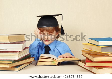 Little boy in academic hat studies an old books - stock photo