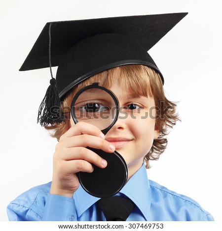 Little boy in academic hat with a magnifying glass on a white background - stock photo