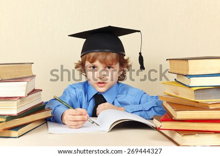 Little boy in academic hat writing pen in a notebook among the old books - stock photo