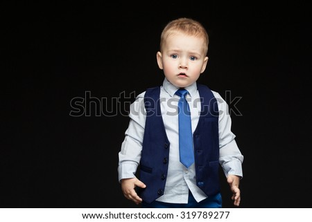 Little boy in blue business suit over black backgound. Copy space. Horizontal. - stock photo