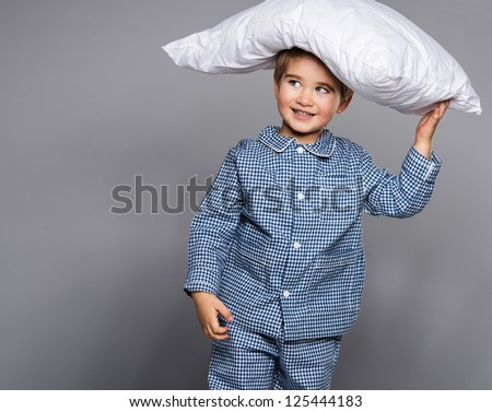 Little boy in blue pyjamas with pillow - stock photo
