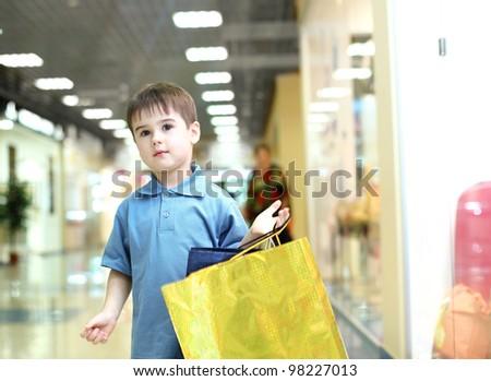 Little boy in blue shirt doing shopping - stock photo