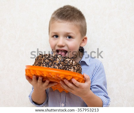 Little boy in blue shirt licking a cake . Close up - stock photo