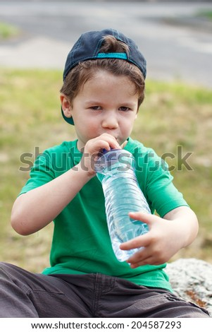 Little boy in cap drinking from water bottle, outdoor portrait - stock photo