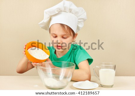 Little boy in chef hat pours flour for baking the cake - stock photo