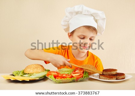 Little boy in chef hat puts meat on the hamburger - stock photo