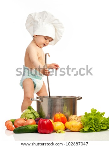 Little boy in chef's hat with ladle, casserole, and vegetables - stock photo