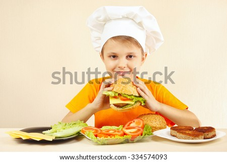Little boy in chefs hat enjoys a cooking hamburger - stock photo