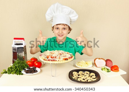 Little boy in chefs hat enjoys a cooking pizza - stock photo