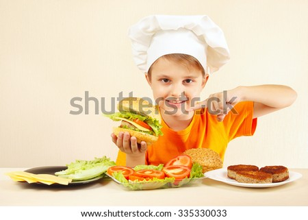 Little boy in chefs hat expressive enjoys a cooked hamburger - stock photo