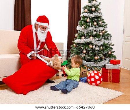 Little boy in Christmas, taking out toys from Santa Claus's bag - stock photo