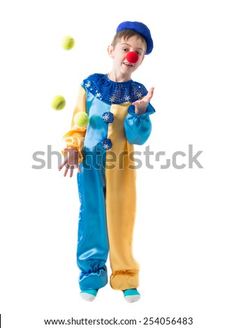Little boy in clown suit juggling three balls and smiling on a white background - stock photo
