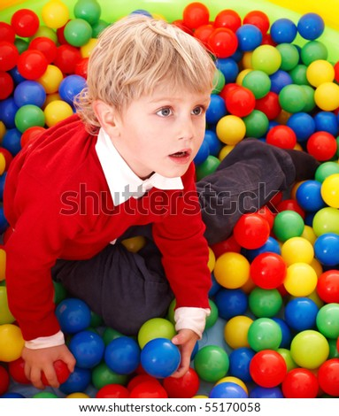 Little boy in colourful balls.  Playground. - stock photo