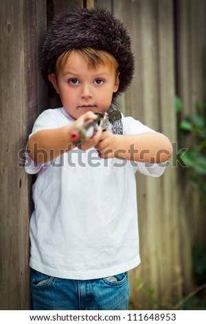 Little boy in coon skin cap pointing his toy rifle - stock photo