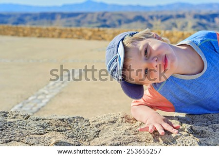 Little boy in denim cap watching on you - stock photo