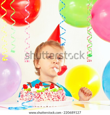 Little boy in festive hat with a birthday cake with whistle and holiday balloons  - stock photo