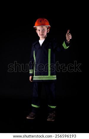 little boy in firefighter uniform  - stock photo