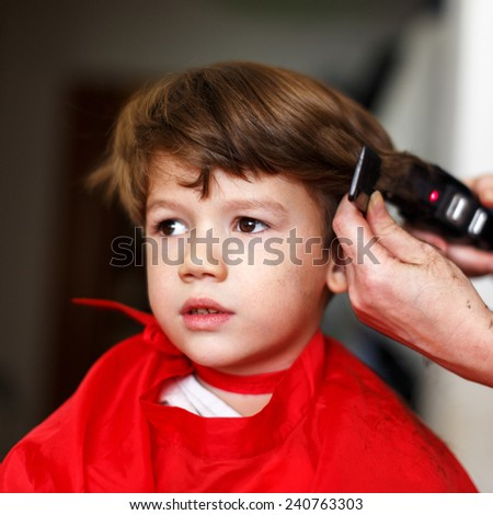 Little boy in hair saloon, haircut, professional barber - stock photo