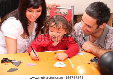 Little boy in Halloween costume with his parents - stock photo