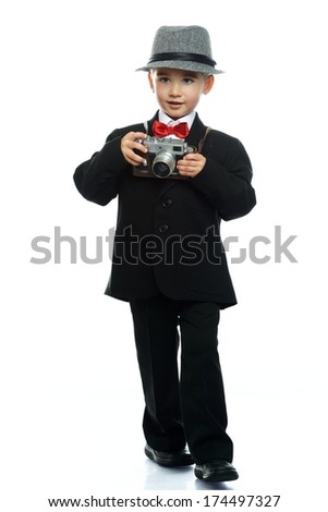 Little boy in hat and black suit with vintage camera isolated on white background  - stock photo