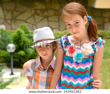 little boy in hat with attractive girl, outdoor portrait - stock photo