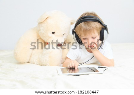 little boy in headset using touch pad with teddy at home - stock photo
