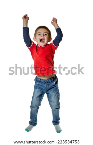 Little boy in jeans and a sweater jumping raising his hands up and mouth open isolated on white background - stock photo