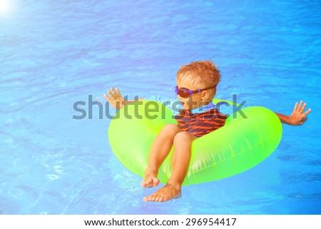 little boy in life ring having fun in the swimming pool - stock photo