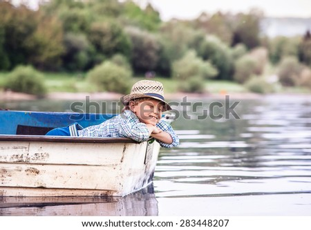 Little boy in old boat on the calm lake surface - stock photo