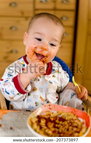 little boy in pajamas eating pasta with tomato sauce with his fingers - stock photo