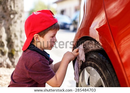 Little boy in red cap cleaning wheel - stock photo