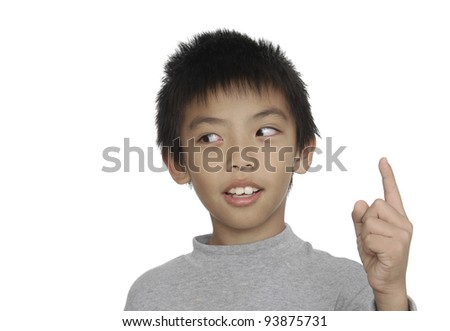 Little boy in round spectacles raising finger in funny attention gesture - stock photo