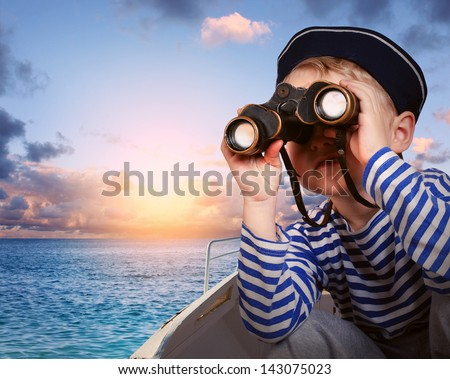 Little boy in sailor's uniform with binocular in the boat - stock photo