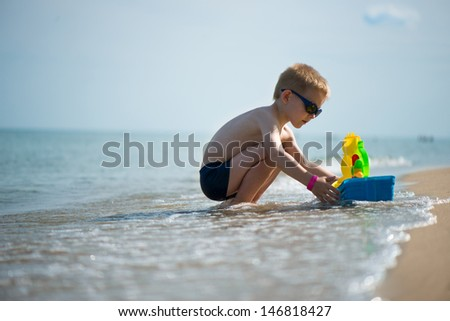 Little boy in sunglasses playing with toy boat at ocean beach - stock photo