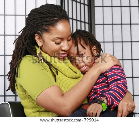 Little boy in tears having a cuddle from his mommy - stock photo