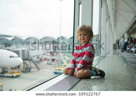 little boy in the airport sitting near the window - stock photo