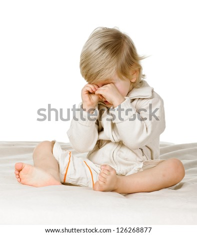 little boy in the bed on white background, he rubs eyes - stock photo
