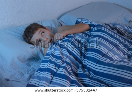 Little boy in the bed scared, hiding under the blanket at night - stock photo