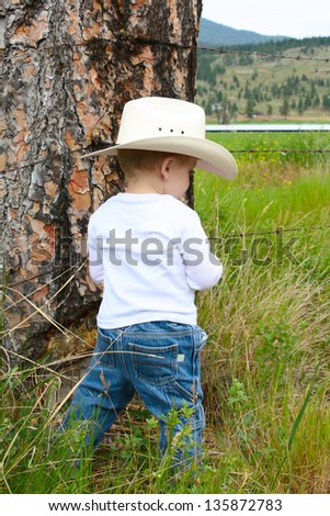 Little boy in the field wearing a cowboy hat - stock photo